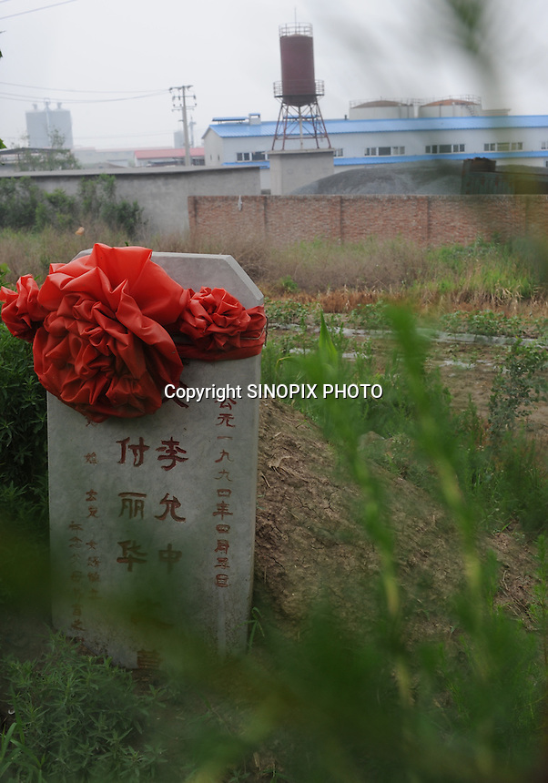 """Grave-stones outside a factory at Xiditou.  A sleent form of protest in the area by those who suffer from cancer is caused by factories in the area is to get buried out-side the factories.  Xiditou is known as one of China's worse """"cancer villages"""" where a reported ten percent have died from cancer."""