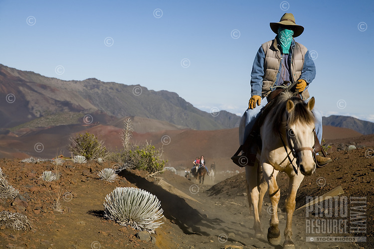 Horseback riding tour guide leading a group of tourists into the Haleakala crater