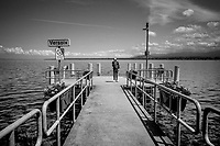 Switzerland. Canton Geneva. Versoix. A lonely man talks on his mobile phone while standing on a boat pier in Lake Geneva. Lake Geneva (French: lac Léman or le Léman) is a deep lake on the north side of the Alps, shared between Switzerland and France. It is one of the largest lakes in Western Europe and the largest on the course of the Rhône. Of it 59.53% (345.31 km2 ) comes under the jurisdiction of Switzerland (cantons of Vaud, Geneva, and Valais), and 40.47% (234.71 km2 ) under France (department of Haute-Savoie).11.06.2020  © 2020 Didier Ruef