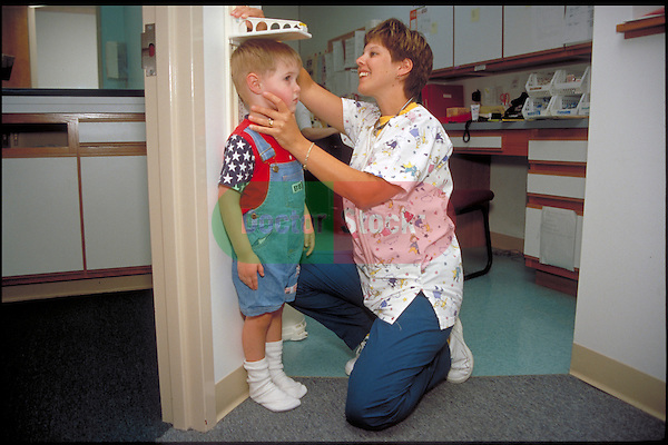 doctor measures height of young boy during examination