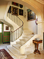 The 18th century stone staircase sweeps up through the centre of the chateau