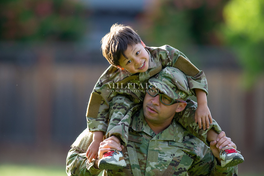 US Military parent spending time with his kids at the park. Stock photo for sale for advertising.