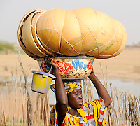 Mali Djenne Frau traegt Kuerbisschalen und Emaille Schale auf dem Kopf zum Markt / MALI , woman carry pumpkin calabash and vessel on the head to the market in Djenné