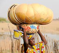 Mali Djenne Frau traegt Kuerbisschalen und Emaille Schale auf dem Kopf zum Markt / MALI , woman carry pumpkin calabash and vessel on the head to the market in Djenné