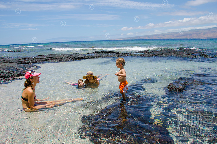 Two local children and their mothers play in the tidal pools at a beach in Puako, South Kohala, Big Island.