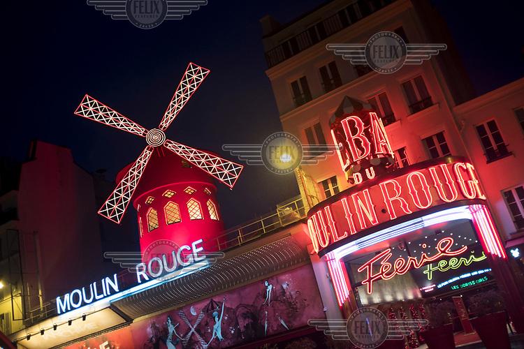 Le Moulin Rouge illuminated at night.