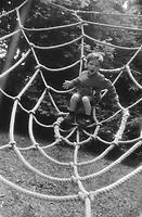 Boy (5-7) on rope spider web (B&W)