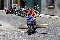 Antigua, Guatemala.  Man Carrying Lumber on his Motorbike.
