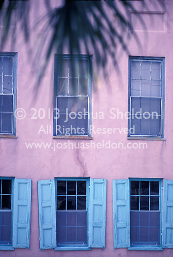 Side of pink building with blue shuttered windows<br />