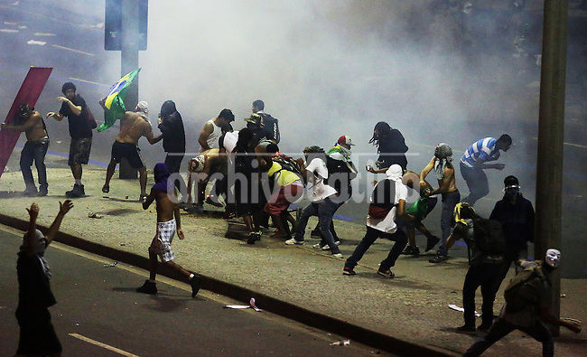 Demonstrators face policemen during the riot on the streets of Rio, in front of the City Hall, Rio de Janeiro, Brazil, June 20, 2013. The people of this movement protest against official corruption and spending on next year's World Cup. (Austral Foto/Léo Corrêa)