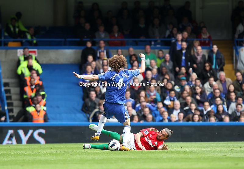 Pictured: Chico Flores with a sliding tackle on David Luiz<br /> Barclays Premier League, Chelsea FC (blue) V Swansea City,<br /> 28/04/13