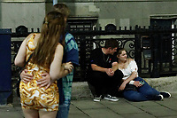 Pictured: A young couple sith on the pavement in Wind Street, Swansea, Wales, UK. Saturday 07 August 2021<br /> Re: Nightclubs have reopened this weekend as most Covid restrictions have come to an end in Wales, UK.<br /> Pubs and restaurants were allowed to open for certain periods, with safety measures in place unlike nightclubs.