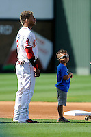 Second baseman Yoan Moncada (24) of the Greenville Drive stands for the National Anthem with a youth player in a game against the Savannah Sand Gnats on Sunday, July 5, 2015, at Fluor Field at the West End in Greenville, South Carolina. The Cuban-born 19-year-old Red Sox signee has been ranked the No. 1 international prospect in baseball by Baseball America. Savannah won, 8-6. (Tom Priddy/Four Seam Images)