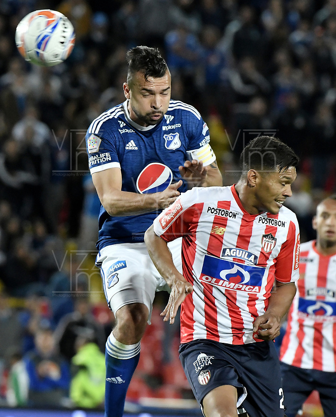 BOGOTA - COLOMBIA, 09-09-2018: Andres Cadavid Cardona (Izq) jugador de Millonarios disputa el balón con Teofilo Gutierrez (Der) jugador de Atlético Junior durante partido por la fecha 9 de la Liga Águila II 2018 jugado en el estadio Nemesio Camacho El Campin de la ciudad de Bogotá. / Andres Cadavid Cardona (L) player of Millonarios fights for the ball with Teofilo Gutierrez (R) player of Atletico Junior during the match for the date 9 of the Liga Aguila II 2018 played at the Nemesio Camacho El Campin Stadium in Bogota city. Photo: VizzorImage / Gabriel Aponte / Staff.