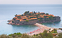The Sveti Stefan Saint Steven island on the Budva Riviera. Sand beach with sun shade umbrellas. Montenegro, Balkan, Europe.