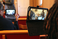 Members of the congregation use electronic tablets to make videos of the Sunday service at The Africa Lighthouse Baptist Temple near Stony Point in Albemarle County, VA. The small 10 family congregation is made up of African refugees and immigrants who's service is spoken in Swahili and translated into English. They've just signed a rent-own lease for a small church after meeting for three years at a local school. Photo/The Daily Progress/Andrew Shurtleff