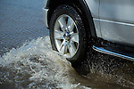 Close up of car driving flooded street