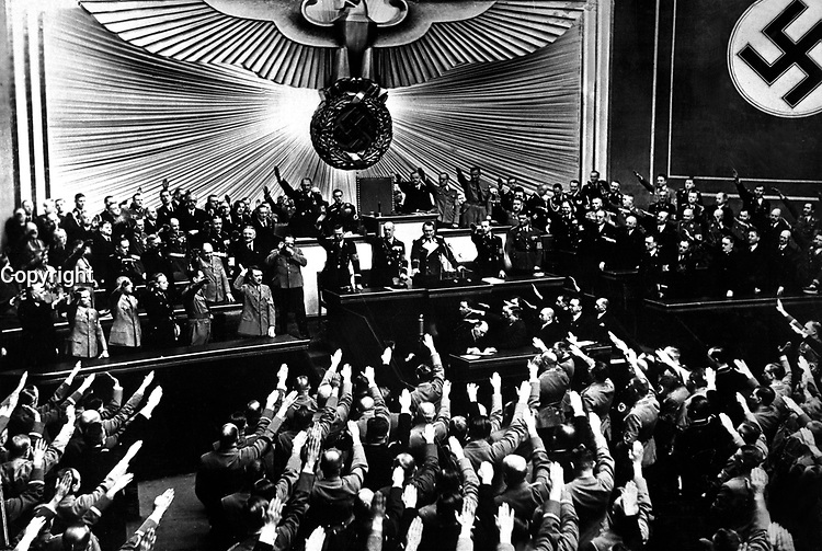 """Hitler accepts the ovation of the Reichstag after announcing the """"peaceful"""" acquisition of Austria.  It set the stage to annex the Czechoslovakian Sudetenland, largely inhabited by a German-speaking population.  Berlin, March 1938.  (OWI)<br /> Exact Date Shot Unknown"""