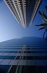 Downtown LA with Library Building reflected in another skyscaper, downtown district, sunny blue sky, Los Angeles, California USA