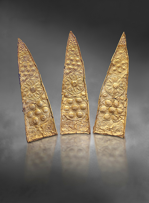 Top leaf shapes of a gold diadem from Grave III, 'Grave of a Women', Grave Circle A, Myenae, Greece. National Archaeological Museum Athens. Grey art Background <br /> <br /> Shaft Grave III, the so-called 'Grave of the Women,' contained three female and two infant interments. The women were literally covered in gold jewelry and wore massive gold diadems, while the infants were overlaid with gold foil.