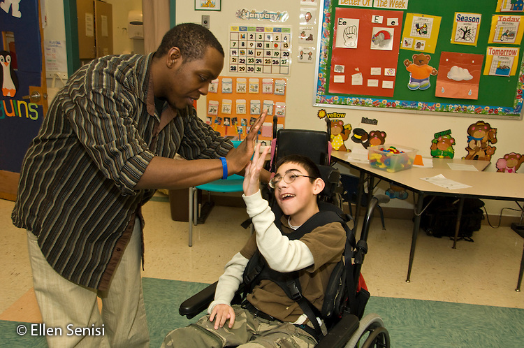 MR/Albany.Langan School at Center for Disability Services (private nonprofit disability services).Upper elementary classroom/Day Program.Teaching assistant slaps five with student in class. Boy: 11, cerebral palsy, expressive and receptive language delays.MR: Bro12, Wes2.© Ellen B. Senisi