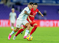 ORLANDO, FL - FEBRUARY 21: Lorena Benitez #16 of Argentina dribbles past Jessie Fleming #17 of Canada during a game between Canada and Argentina at Exploria Stadium on February 21, 2021 in Orlando, Florida.