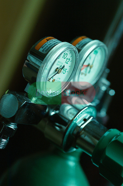 pressure gauges on top of green oxygen tank