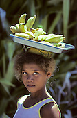 Bahia State, Brazil. Girl carrying a tray of bananas on her head.