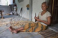 Yogyakarta, Java, Indonesia.  Old Woman Preparing Palm Frond Strips for Basket-Making.