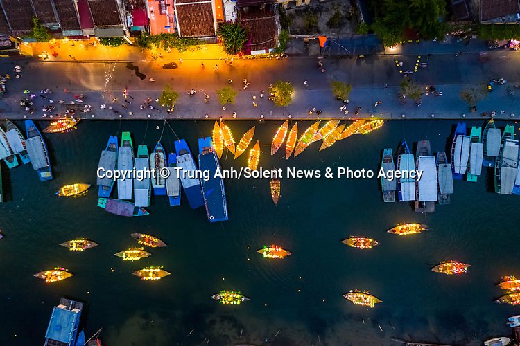 """A fleet of glowing boats transport tourists along a canal in Hoi An, Vietnam.<br /> <br /> The luminous vessels were captured from above by  photographer Trung Anh.<br /> <br /> Trung said, """"To stimulate tourism following the coronavirus pandemic, boat owners have decorated their boats like this to make them more attractive.  I think they look like leaves floating in the river.""""<br /> <br /> Please byline: Trung Anh/Solent News<br /> <br /> © Trung Anh/Solent News & Photo Agency<br /> UK +44 (0) 2380 458800"""