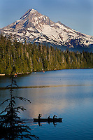 A fine art landscape image of canoers silhouetted at sunset, paddling across a lake in the foreground, with pines and Mount Hood, Oregon, beyond.  The white snow on Mt. Hood and and blue sky in the background contrast with the deeper blue color of the lake.