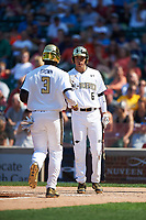 Dylan Carlson (6) of Elk Grove High School in Elk Grove, California fist bumps AJ Brown (3) of Starkville High School in Starkville, Mississippi after scoring on a home run by Andy Yerzy (not shown) during the Under Armour All-American Game on August 15, 2015 at Wrigley Field in Chicago, Illinois. (Mike Janes/Four Seam Images)