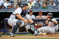 Baltimore Orioles infielder Robert Andino #11 scores run while New York Yankees catcher Russell Martin #55 tries to block home plate during game at Yankee Stadium on September 5, 2011 in Bronx, NY.  Yankees defeated Orioles 11-10.  Tomasso DeRosa/Four Seam Images