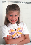 portrait of 7 year old girl missing teeth butterfly on shirt vertical