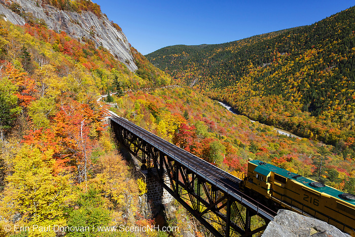 """Conway Scenic Railroad's """"Notch Train"""" crossing the Willey Brook Trestle along the old Maine Central Railroad in Hart's Location, New Hampshire during the autumn months. The Willard section house was located just beyond the trestle. This trestle is within Crawford Notch State Park. And since 1995 the Conway Scenic Railroad, which provides passenger excursion trains has been using the track."""