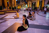 Women devotees pray in the Shwedagon Pagoda.