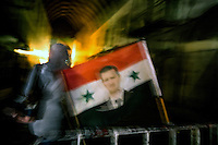 A Syrian flag with the face of President Bashar al Assad at a military checkpoint in the old town of Damascus, Syria. Checkpoints have become a fact of daily life in the Syrian capital as car bombs and suicide bombers have continually targeted all areas of the city.
