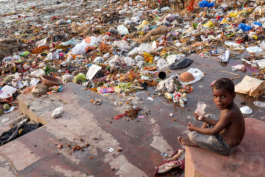 Young Boy eating among the Garbage and Plastic that accumulated at the banks of the Ganges River at the Babu Ghat, an environmental problem. Ganges River Kolkata, India