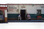 ELDERLY MAN AND WOMAN RELAX IN SHADE OUTSIDE STORE IN MEXICO