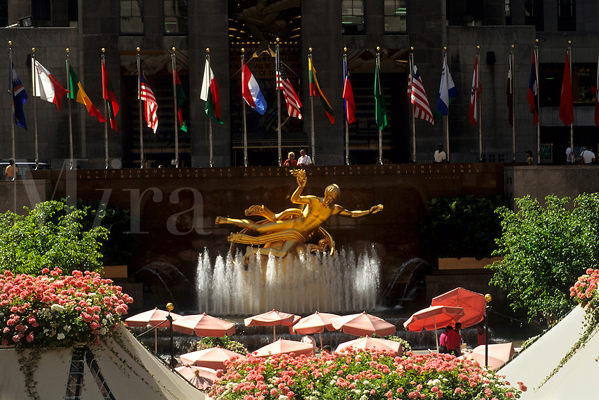 Famous RCA gold statue in Rockefeller Center with flags and flowers and cafe in New York City USA