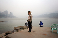CHINA. Sichuan Province. Chongqing. A woman stands on the banks of the Yangtze river which is at its lowest for the past 150 years as a result of a nationwide drought. Chongqing is a city of over 3,000,000 people, famed for being the capital of China between 1938 and 1946 during World War II. It is situated on the banks of the Yangtze river, China's longest river and the third longest in the world. Originating in Tibet, the river flows for 3,964 miles (6,380km) through central China into the East China Sea at Shanghai.  2008