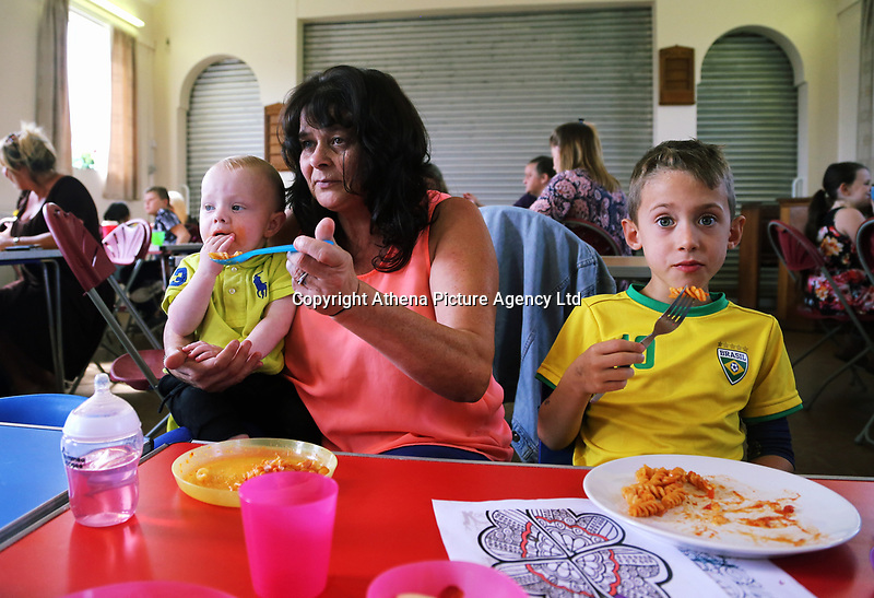 Pictured: Heather Maynard (C) feeds one year old Lincoln (L) and joined by Ben, 6 at St Teilo Church in Clase, Swansea, UK. Friday 25 August 2017<br /> Re: Free food for children story, Swansea, Wales, UK.