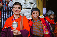 Colurful Buddhist lady spinning a prayer wheel with her family and friends at a religious and social gathering, National Memorial Choeten, Thimpu, Bhutan