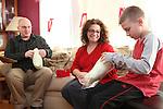 WATERBURY, CT-27 December 2013-122713LW03 - From left, Greg Artman, Julianne Artman and nine-year-old Mason Artman sew pillows for cancer patients Dec. 27 in their Waterbury home.<br /> Laraine Weschler Republican-American