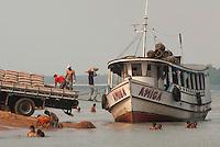 Embarcação chega a cidade para embarcar mercadorias que serão levadas para comunidades mais distantes aportando onde moradores tomam banho no rio Tocantins.Tucuruí, Pará, Brasil.Paulo Santos29/10/2010