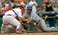 New York Mets Ramon Castro, right dives head first into home plate and beats a late tag by Phillies catcher Rod Barajas, left, and scores on a RBI single by teammate Orlando Hernandez in the fourth inning Friday, June 29, 2007, in Philadelphia. Mets beat the Phillies 6-5. Bradley C Bower/Bloomberg News