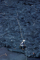 Telephone repair woman working on lines in hardened lava. Kalapana, Big Island