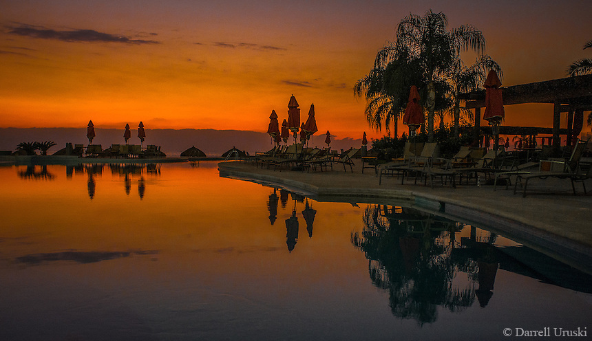 Fine Art Landscape Photograph. Sunset on Banderas Bay, Puerto, Vallarta, Mexico. Grand Venitian pool. Silhouettes and pool reflections from the golden rays of the setting sun.