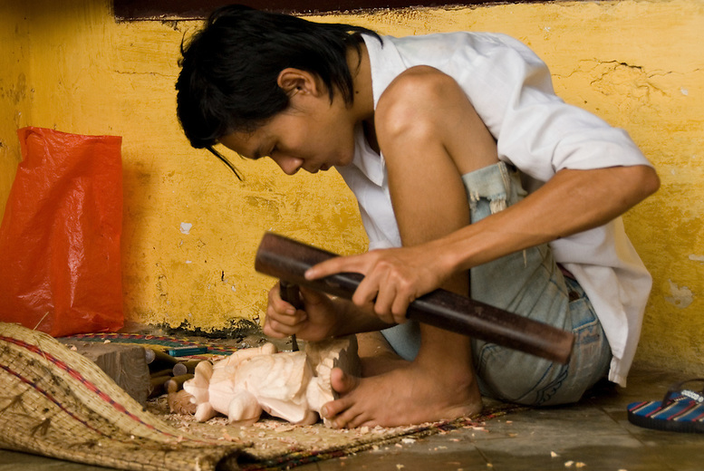 A young Vietnamese artisan carving a sculpture. The small island of Cam Kim just outside Hoi An is known for its handicraft.