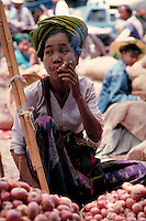 In a Rangoon, Myanmar, food market, a woman smoking a cigar waits for customers. food, street scene, trade, occupations, vendor, Burma. woman food merchant. Rangoon, Myanmar street food market.